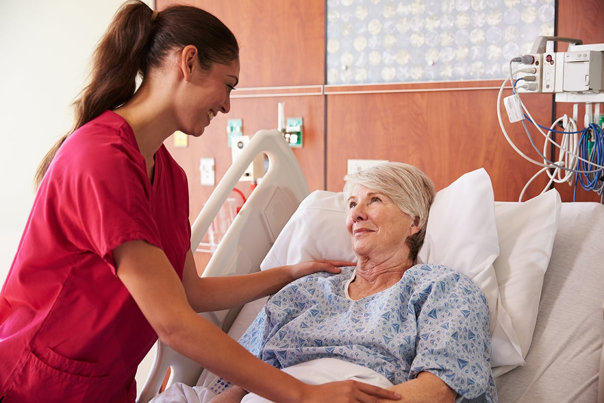 nurse with older patient in hospital bed